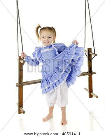 An adorable, barefoot preschooler lifting her pretty, old-fashioned dress, showing off her bloomers.  She holds onto the ropes of an antique wooden, 2-person swing.  On a white background.