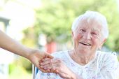 stock photo of grandmother  - Happy senior woman holding hands with caretaker - JPG