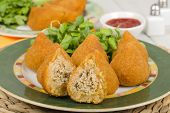 foto of brazilian food  - Coxinha de Galinha - Brazilian breaded and deep fried snack filled with shredded chicken served with chili dip. ** Note: Shallow depth of field - JPG