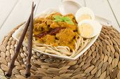 pic of ayam  - Dry Curry Mee - Malaysian chicken curry with coconut milk and noodles served with boiled egg on a woven mat.