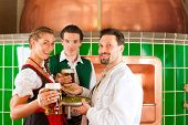 Man and woman in Bavarian Tracht with male brewer, hops and beer stein in brewery