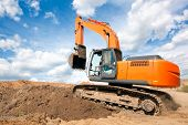 stock photo of earth-mover  - Excavator machine moves with raised bucket on construction site during earth moving works - JPG