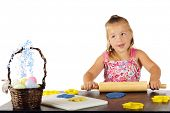 An adorable preschooler rolling out kiddie dough for cutting out with Easter-shaped cookie cutters.
