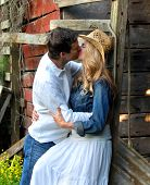 stock photo of denim wear  - Couple share a romantic kiss leaning against a rustic red wooden barn. She is wearing a denim jacket and white dress. He is wearing jeans and a white shirt.