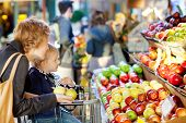 stock photo of department store  - mother and her son buying fruits at a farmers market - JPG