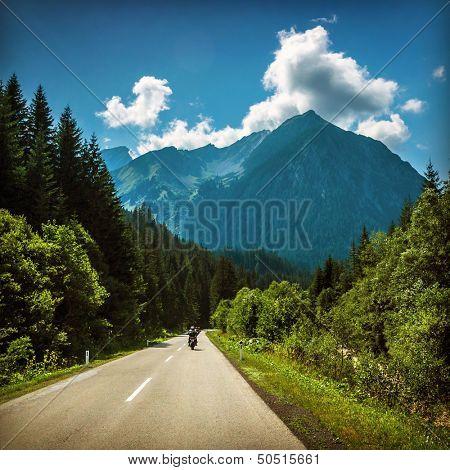 Motorcyclist riding on mountainous highway, Euro tour on motorbike, road pass along Alps mountains, extreme sport, freedom concept