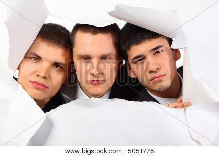 Three Young Men Looking Out In Hole In Paper