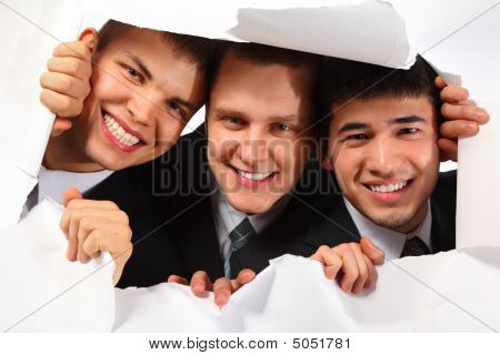Three Young Smiling Men Looking Out In Hole In Paper