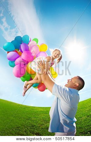 Father throws daughter. Family playing together in park with balloons. Father tosses a baby against the sky