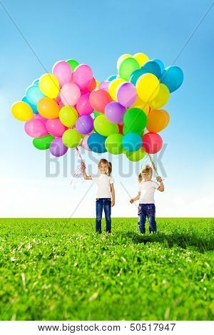 Happy little girl holding colorful balloons. Child playing on a green meadow. Smiling  kid.