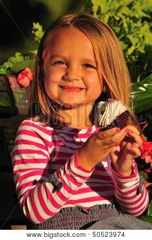 Little Girl Eating Sweet Cupcake
