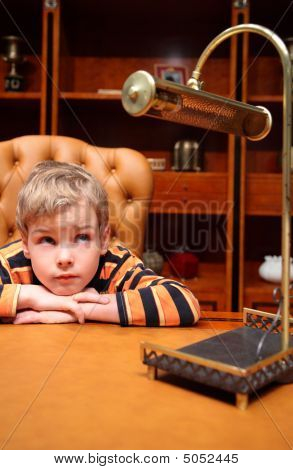 Boy Sits In Luxury Office