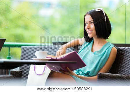 Girl wearing blue dress and sunglasses sits at the table of the bar and reads book with cup of tea