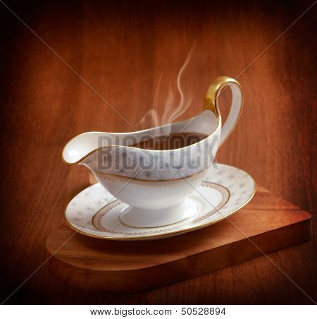 Rich steaming gravy served in gravy boat on wooden board