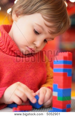 Little Girl Plays With Plastic Constructor