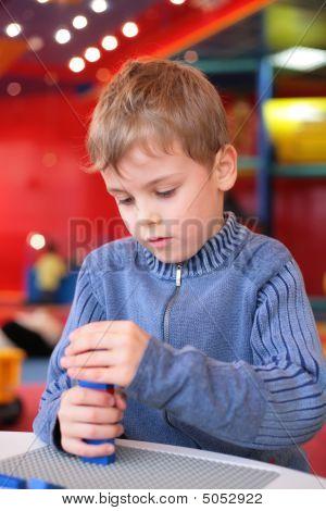 Boy spielt mit Kunststoff-Konstruktor im kindergarten