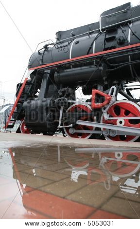 Steam Locomotive And Its Reflection In  Puddle