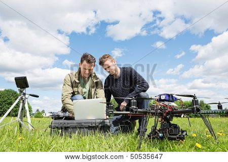Young male technicians working together on laptop by UAV helicopter and tripod in park