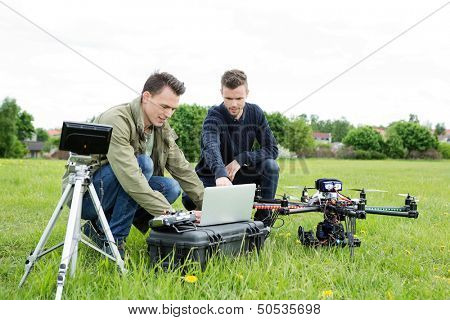 Young male technicians using laptop by tripod and UAV octocopter in park