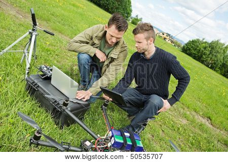 Young male engineers discussing over digital tablet and laptop by UAV drone in park