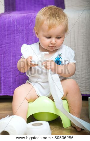 adorable baby on the potty with toilet paper