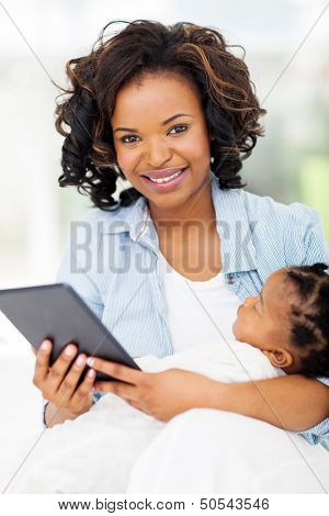 pretty young african mother holding tablet computer with baby at home