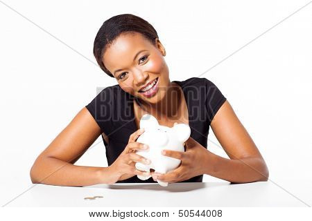 happy african woman holding piggybank looking at the camera