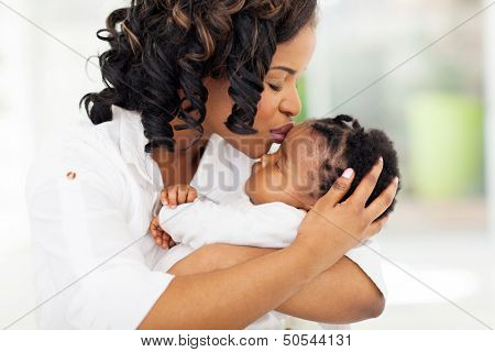 loving african american woman kissing her baby girl