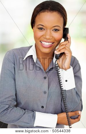 happy african businesswoman using landline phone