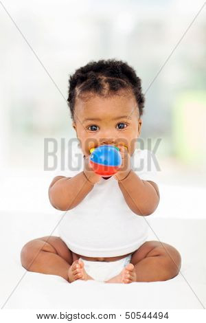 cute african baby girl biting her toy