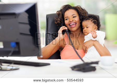 successful african businesswoman talking on landline phone while holding her little baby girl