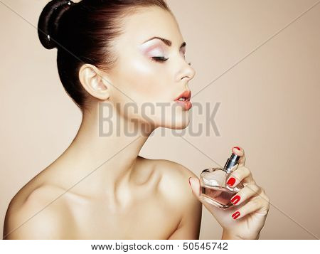 Young Beautiful Woman With Bottle Of Perfume. Perfect Makeup