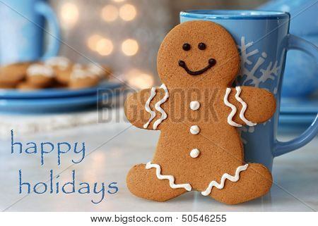 Holiday greeting card with smiling gingerbread man standing next to snowflake mug.  Plate of additional cookies and defocused holiday lights in background.