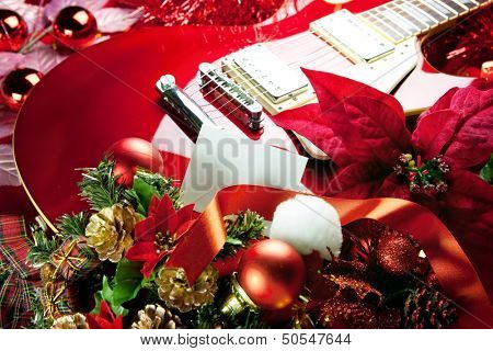 Red electric guitar with white blank card in front for your message. Concept image for holiday musical event.