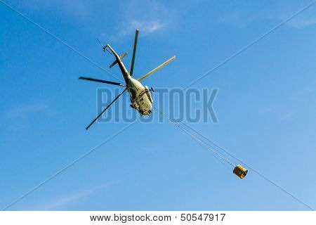 Helicopter in action carrying the water bucket. Shot from the below.