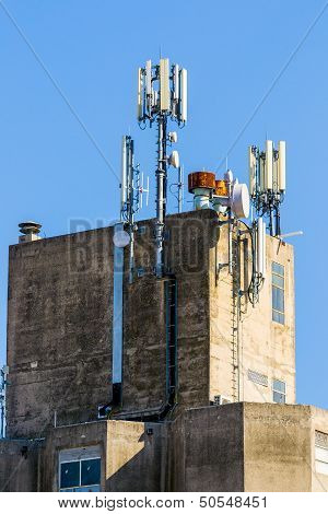 Industrial building with GSM antennas on roof isolated on blue sky.