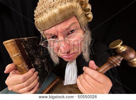 Malhumorado viejo juez en primer plano extremo angular con martillo y peluca