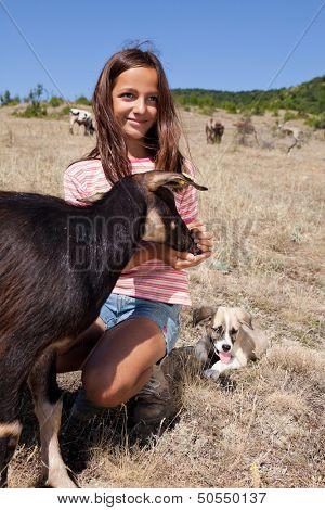 Cattle shepherd girl feeding a goat in the Bulgarian mountains