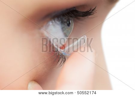Extreme close up on young model applying contact lens on her blue eyes