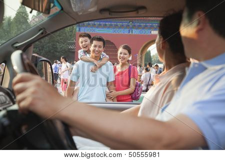 Grandparents driving and saying good bay to grandson and parents