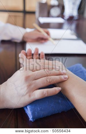 Close Up of Patient's Hand While Doctor Takes Pulse