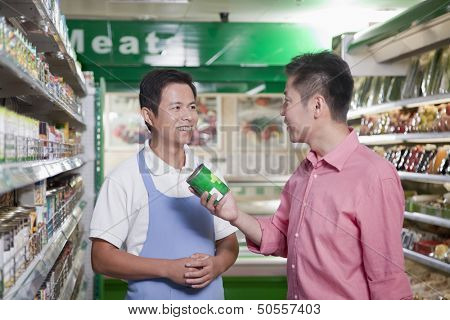 Sales clerk assisting man in supermarket, Beijing