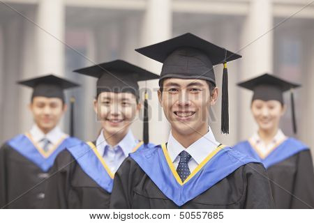 Four University Graduates Smiling, Looking at Camera