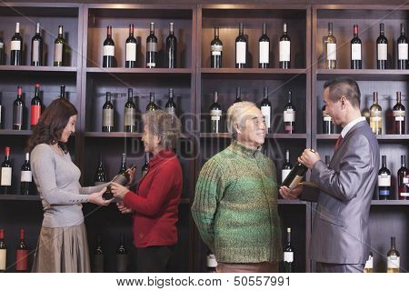 Four People Examining Wine at a Wine Store