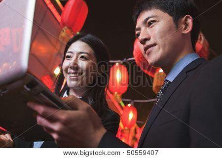 Coworkers working at night, City street, red lanterns on the background