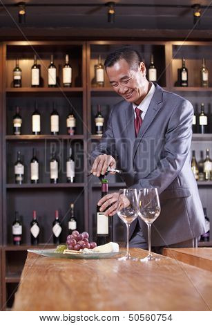 Businessman Opening Wine Bottle