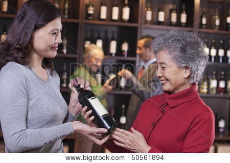 Two Women Examining Wine at a Wine Store