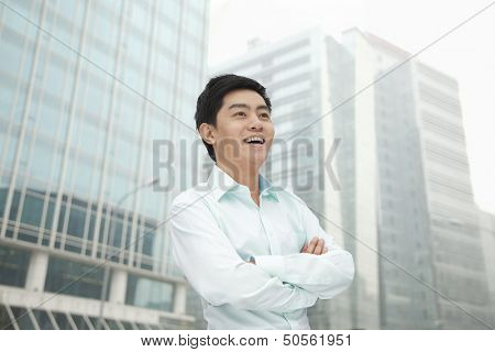 Portrait of young businessman in button down shirt with arms crossed, outdoors, Beijing
