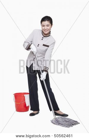 Young female caretaker cleaning with bucket and mop, studio shot