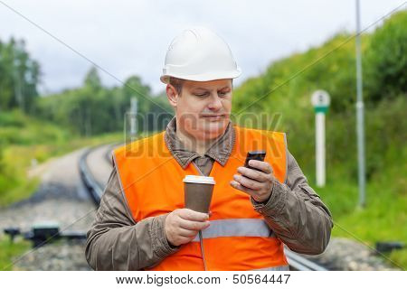 Worker with cell phone and coffee on the railway